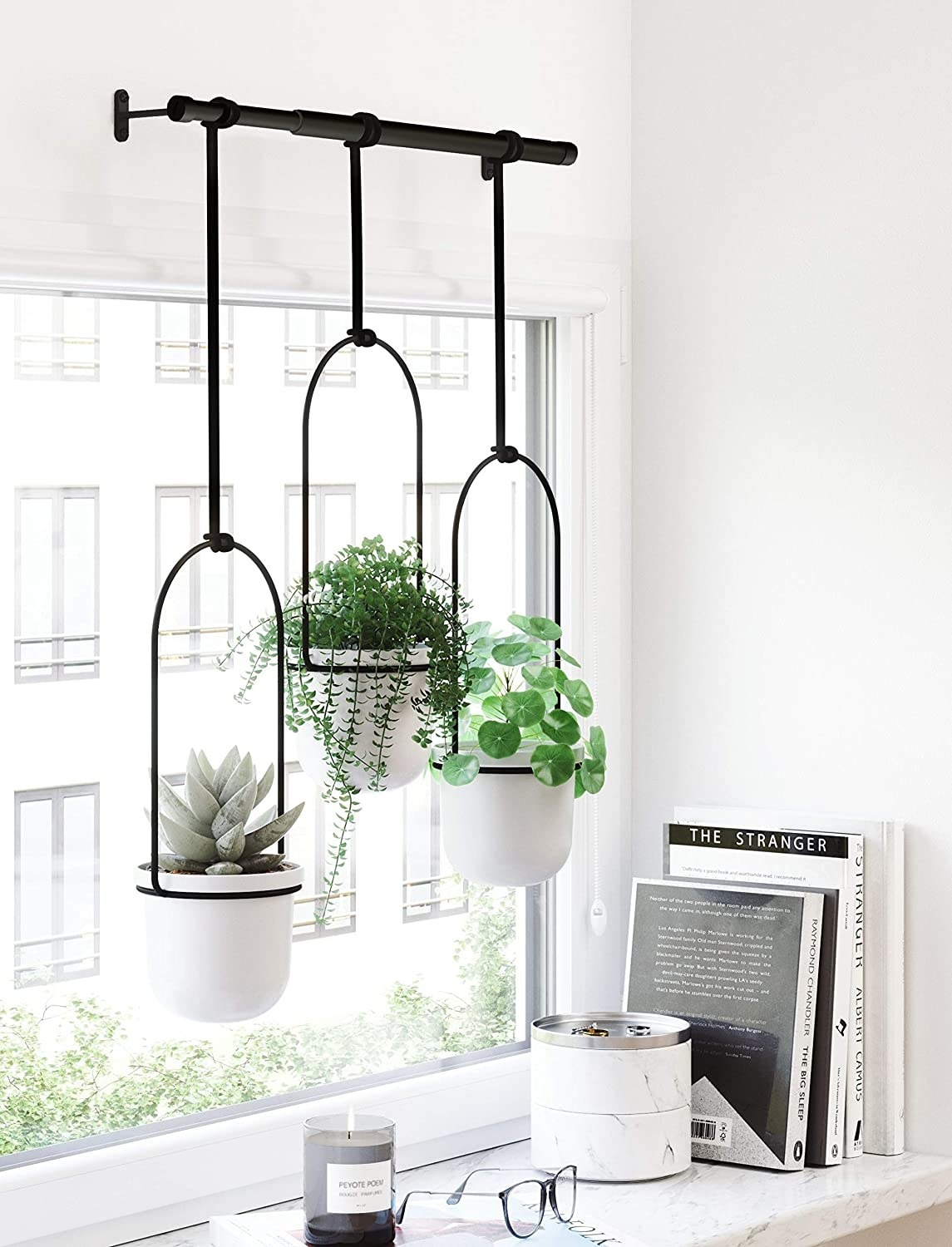 three white planters held up by a black bar