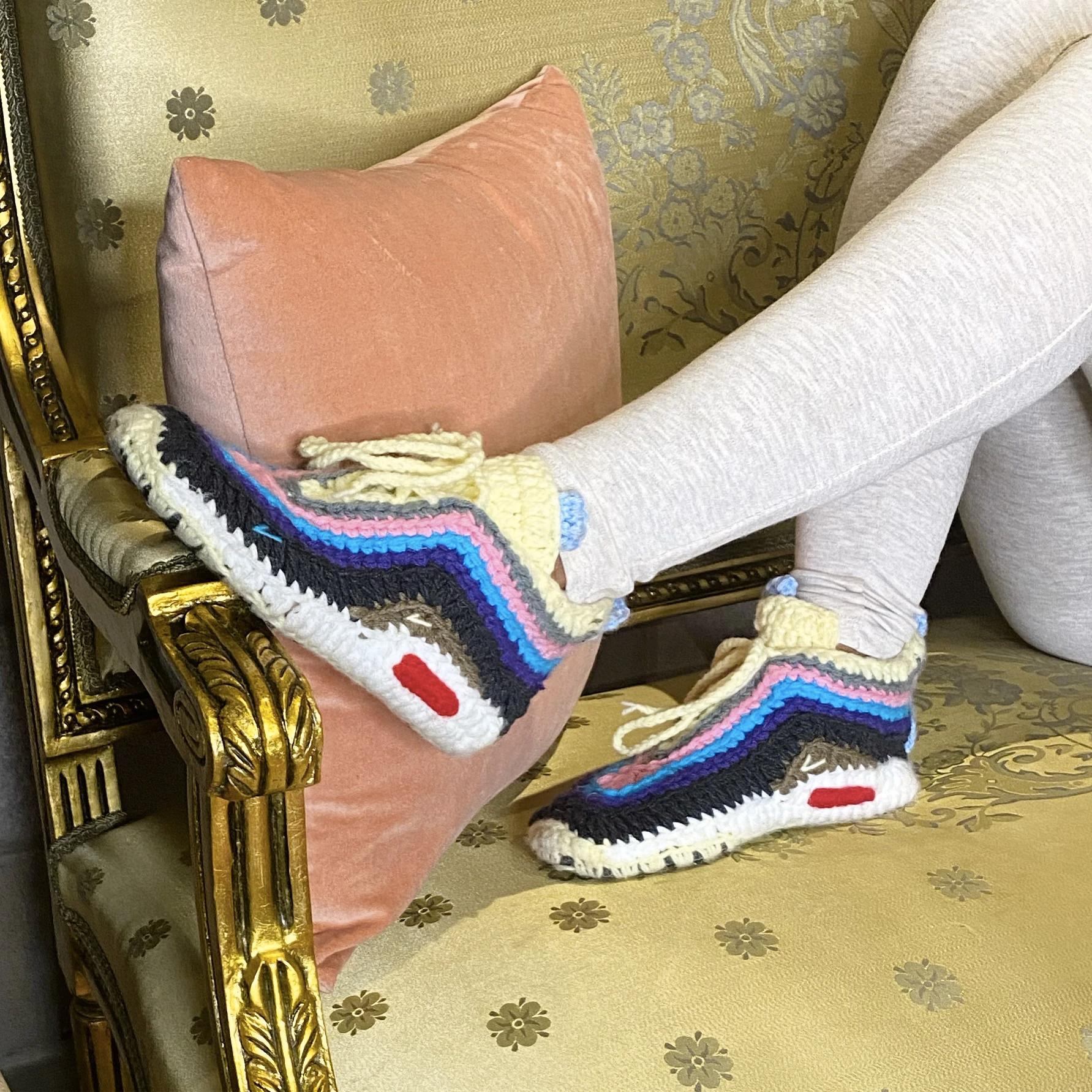 models wears knit slippers shaped like sneakers