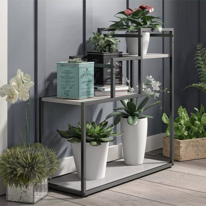 A tiered plant stand with wooden shelves and metal frame