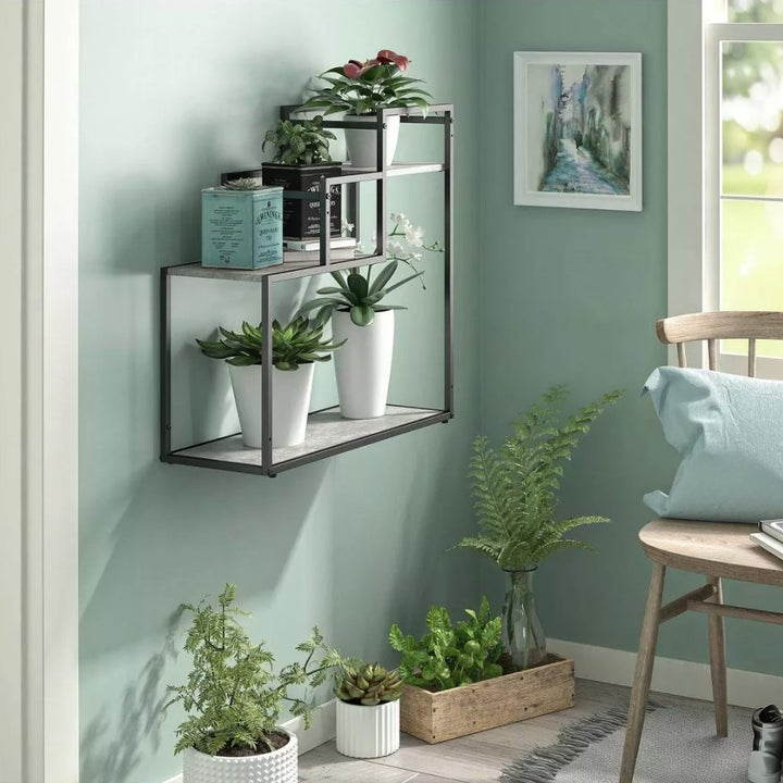 A tiered plant stand with wooden shelves and metal frame mounted up on a wall
