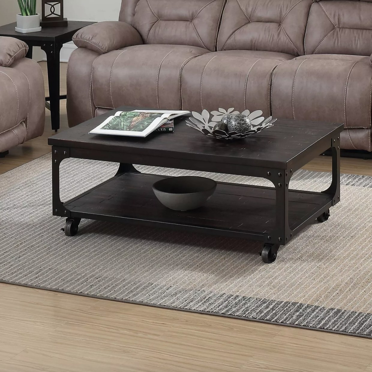 A dark wood coffee table with metal frame, lift top, and caster wheels