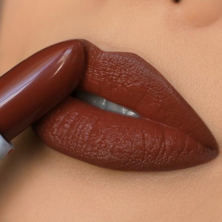 a dark burgundy/orange lipstick being applied