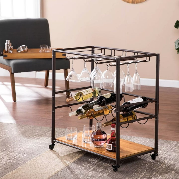 A bar cart with metal frame, wooden shelves, bottle, and glass storage