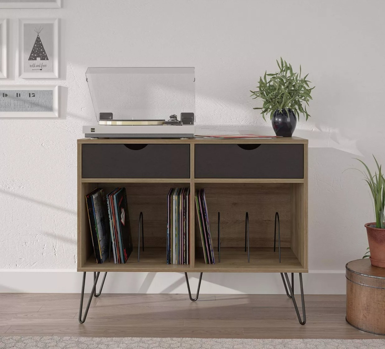 A wooden turntable stand with hairpin legs, drawers, and space for vinyl records