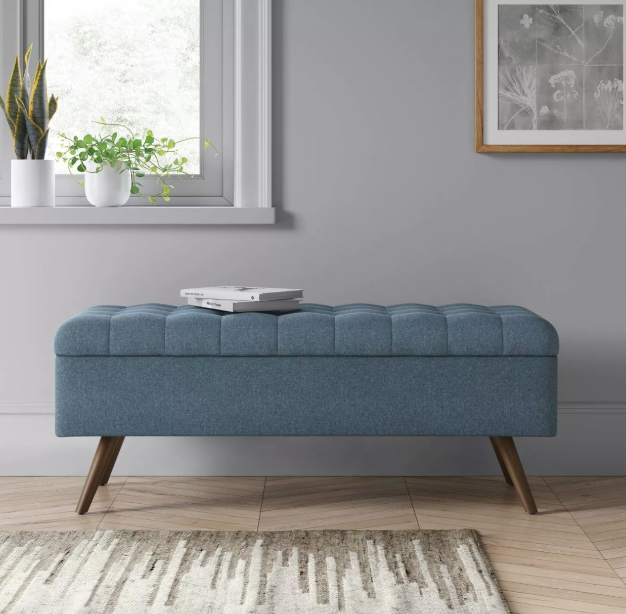 A blue tufted storage bench with wooden legs