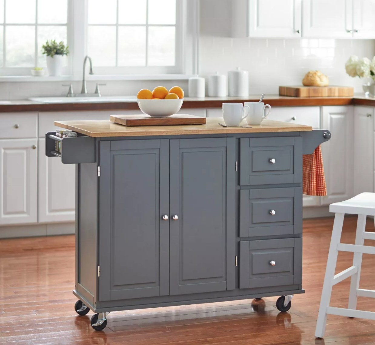 A gray kitchen island cart with wooden top and storage cabinets and drawers