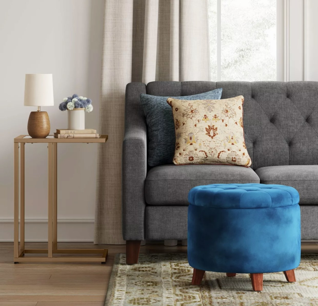 A blue velvet tufted storage ottoman with wooden legs