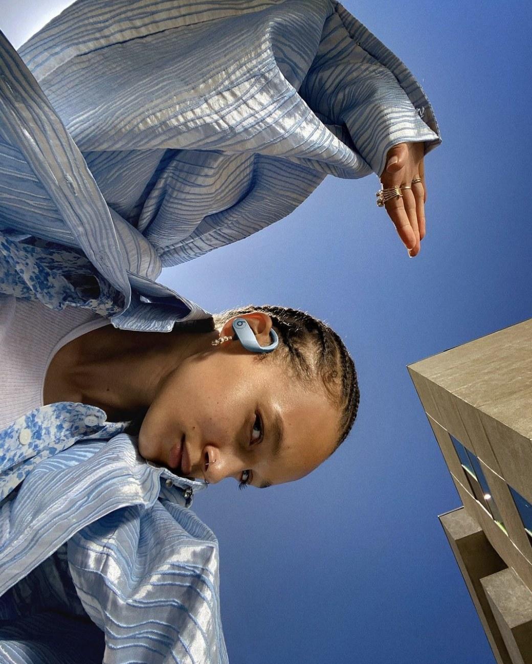A model wearing the PowerBeats in blue