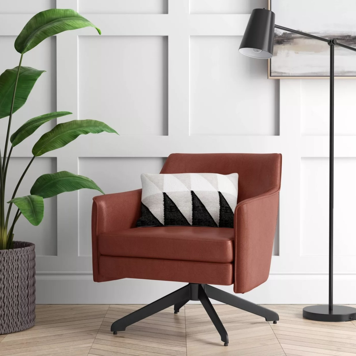 A brown faux leather accent chair with black metal swivel base