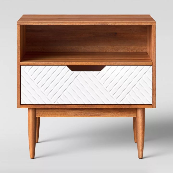 A brown wooden side table with white drawer front and geometric design