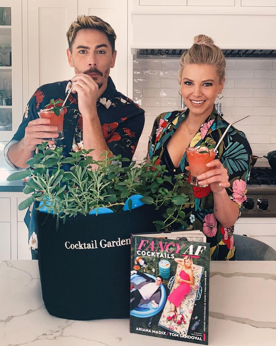 tom and ariana holding drinks with a cocktail garden kit and their book in front of them