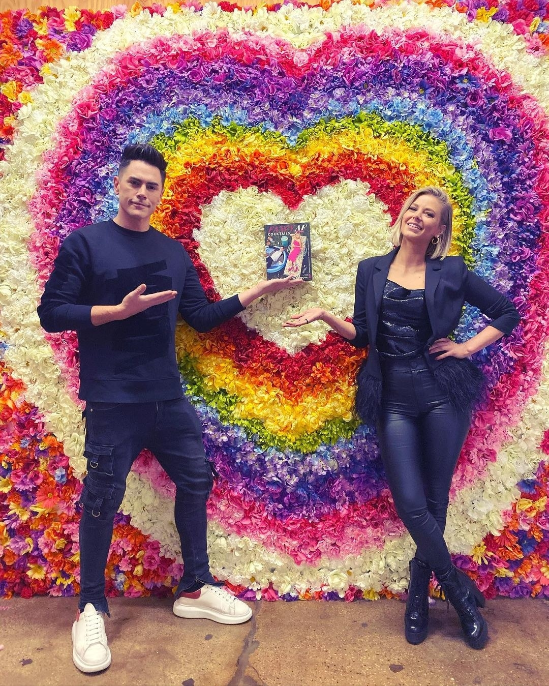 tom and ariana holding their book