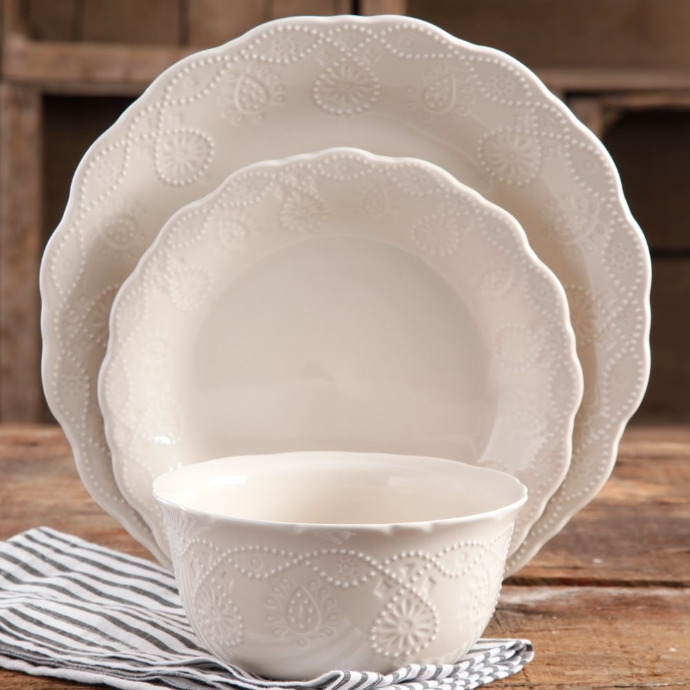 a ceramic bowl, salad plate, adn dinner plate with a dotten design along the rims of each resting on a counter