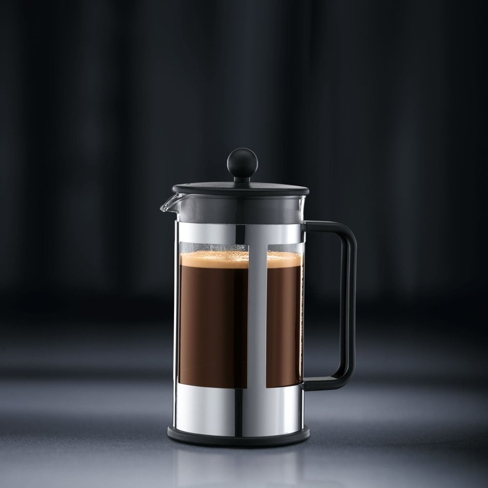 a silver and black French press holding freshly brewed coffee