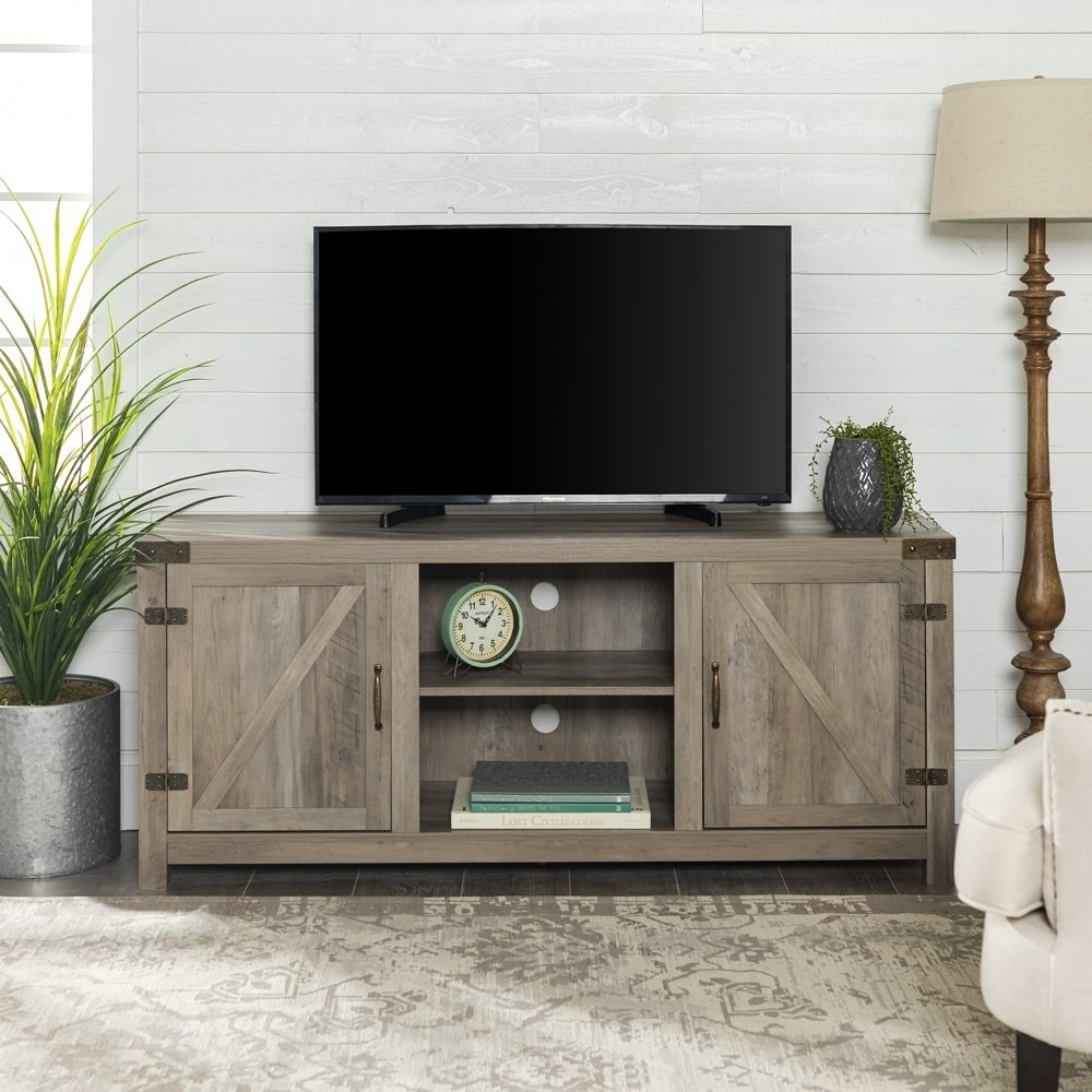 a light beige tv stand with two barn doors, two shelves for storage, with a TV sitting on top