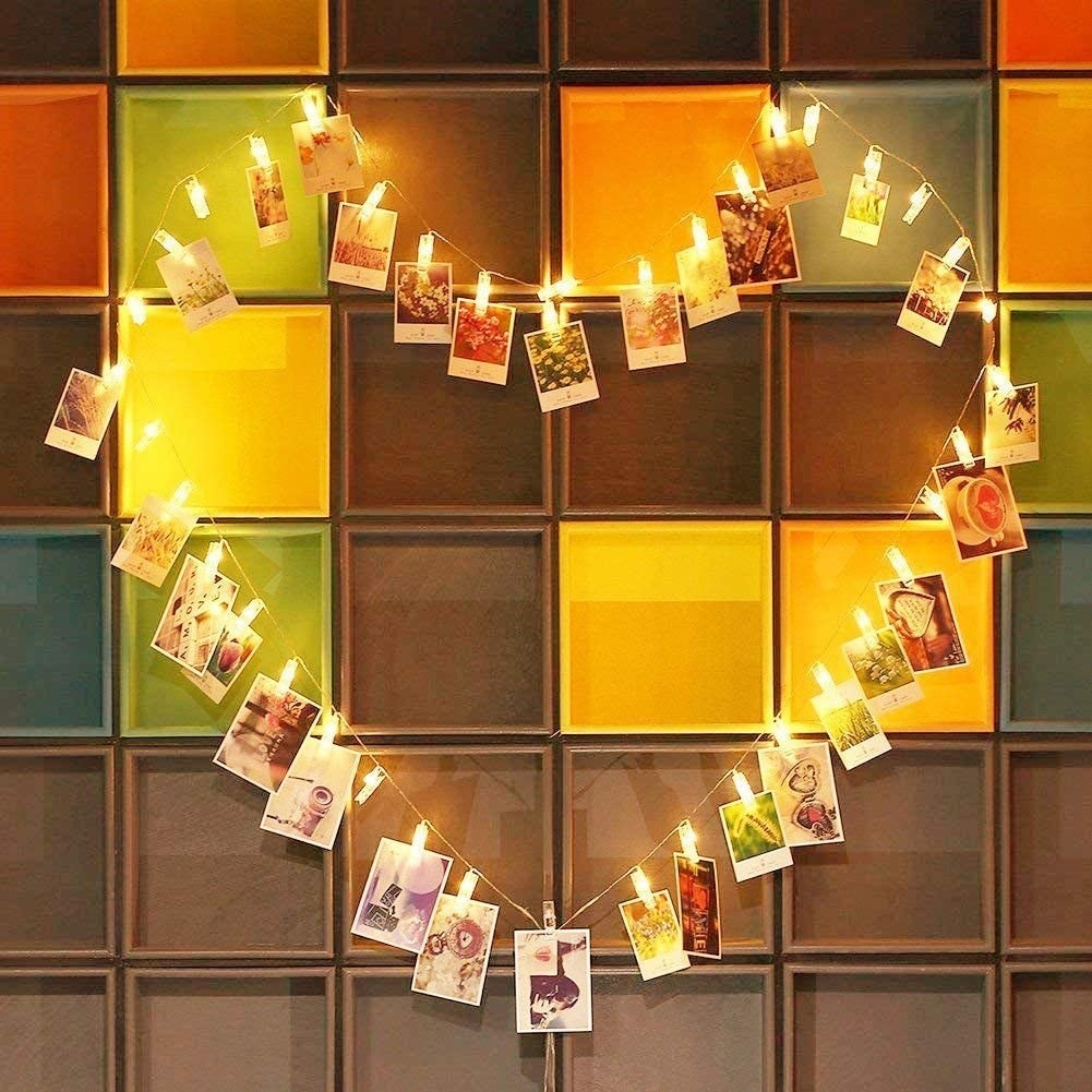 Glowing fairy lights in the shape of a heart with pictures hanging from them