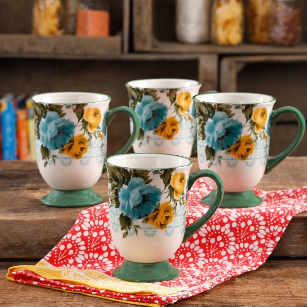four latte mugs with tea bases and handles, with blue and yellow roses painted on the cup