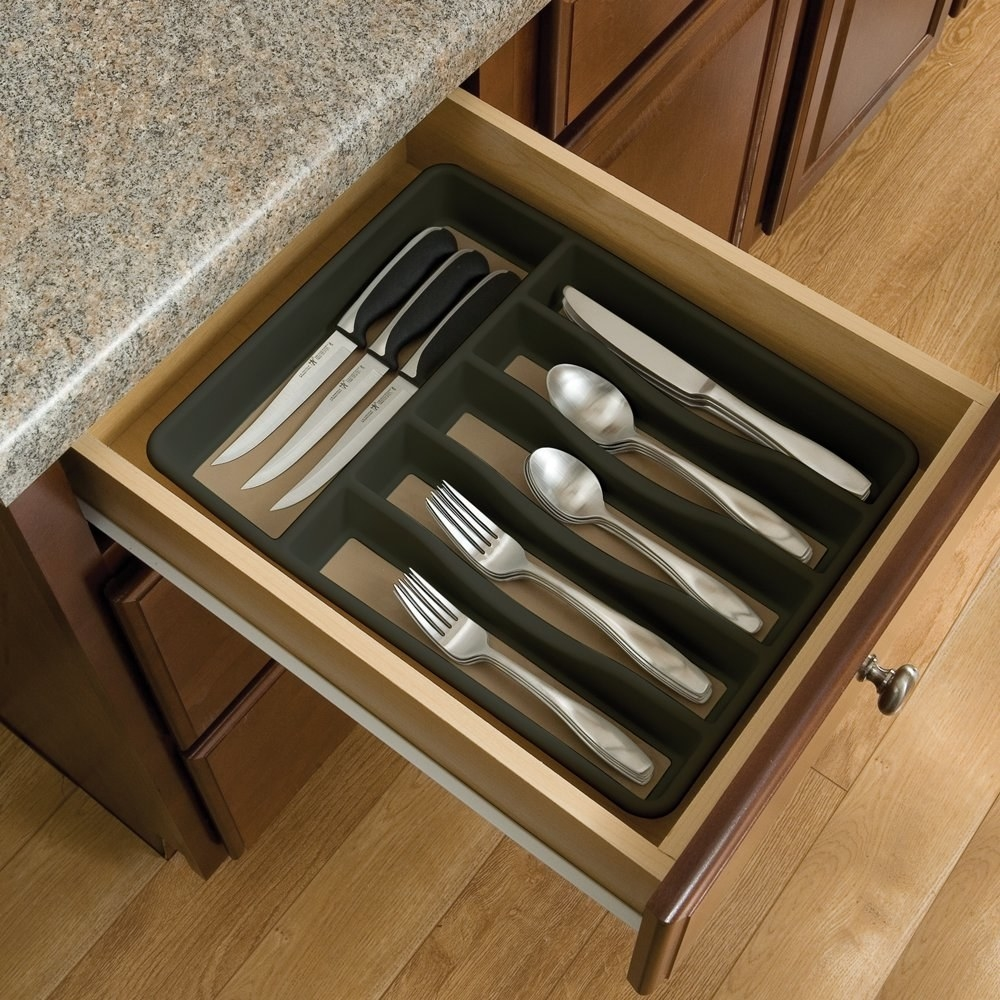 a grey cutlery organier in a drawer holding forks, knives, and spoons