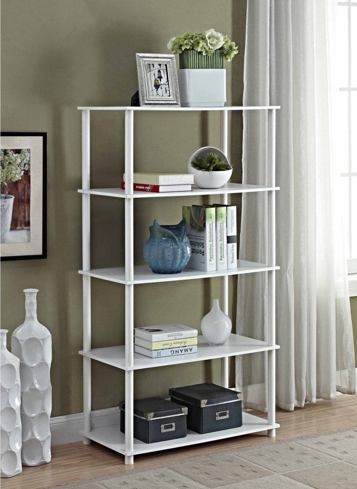 a white bookshelve with 5 shelves in a living room.