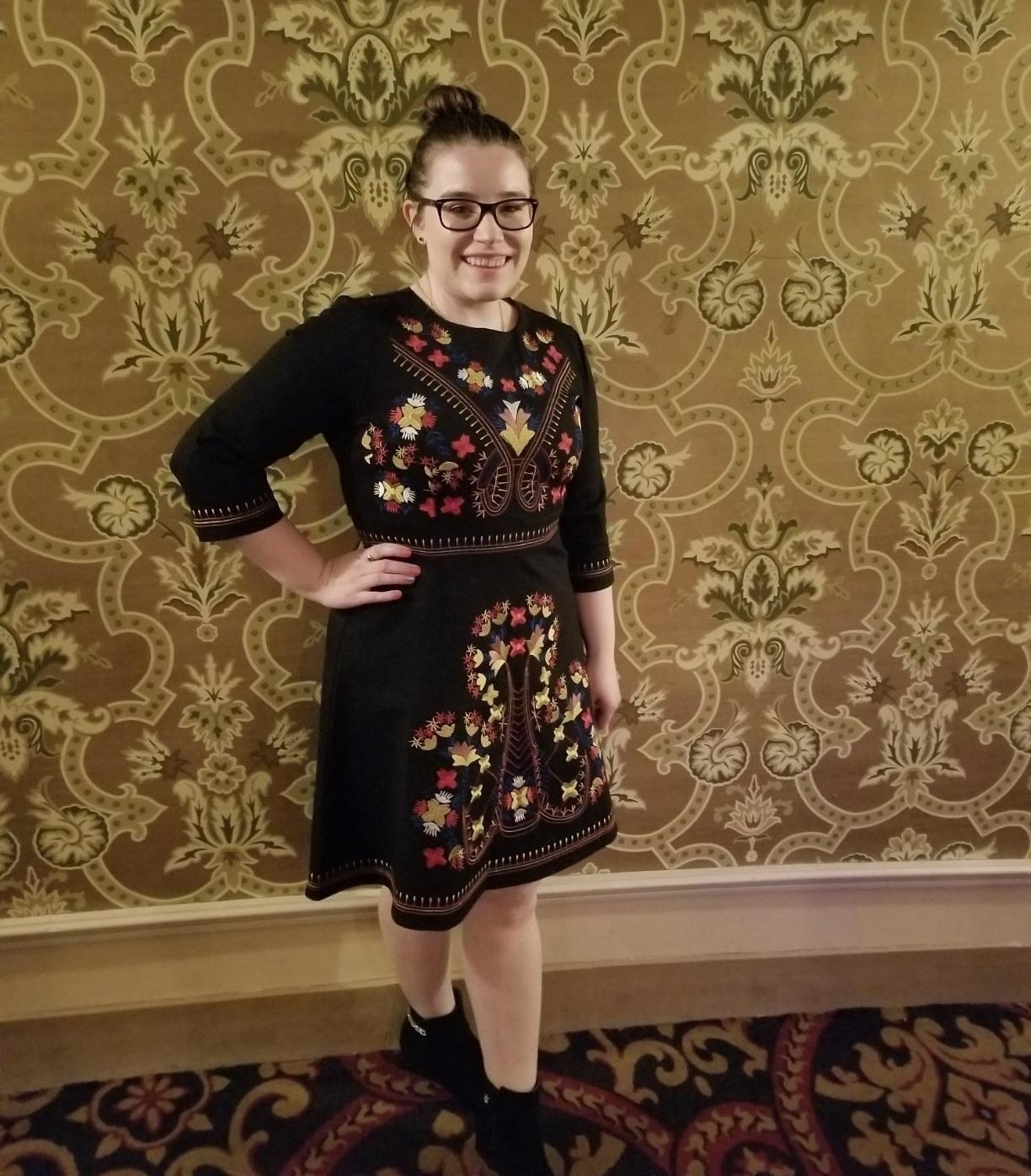 Reviewer wearing the knee-length black dress with yellow, red, and brown embroidery on it