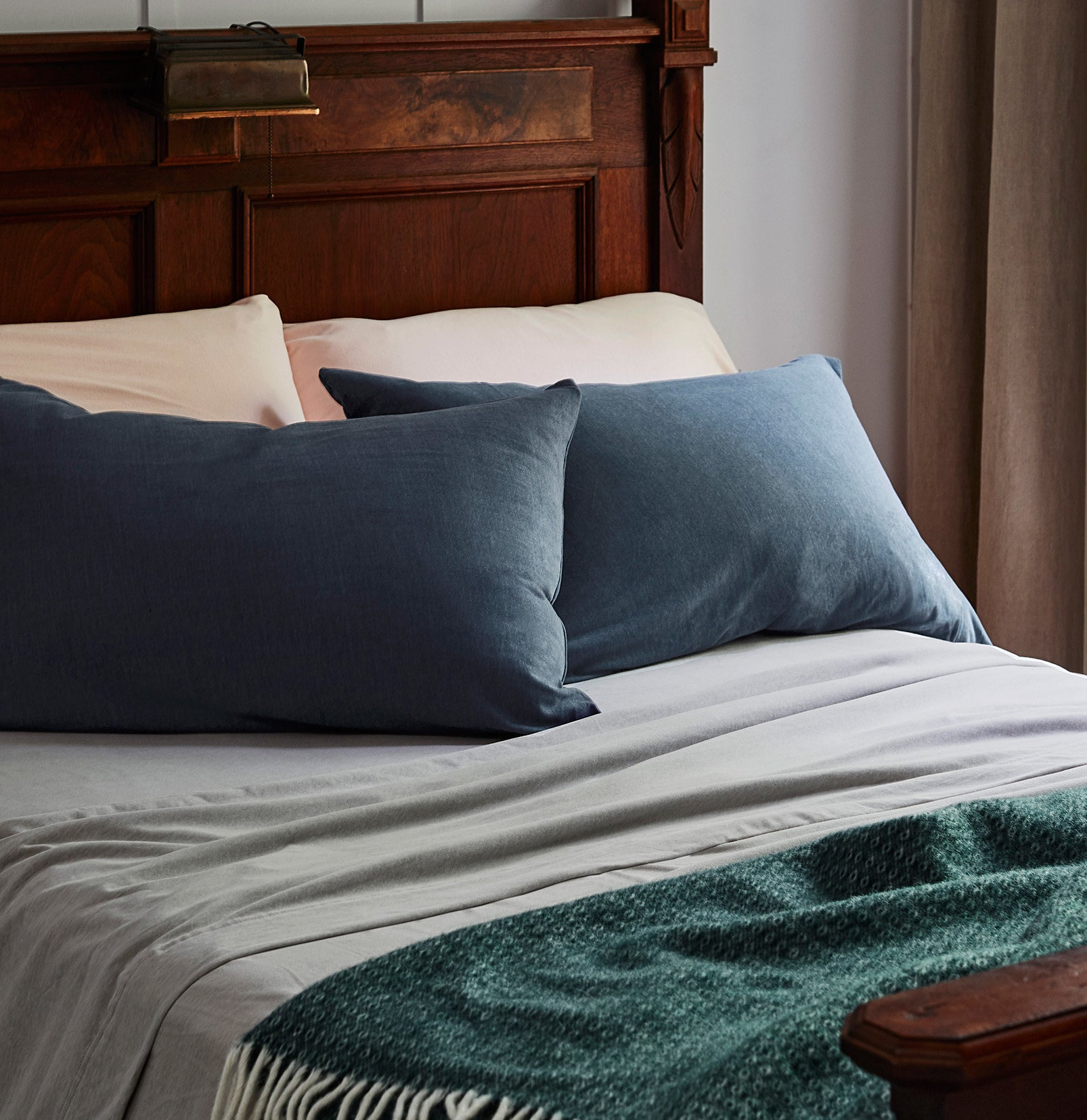 A cozy bed with pillows, pillowcases, sheets, and a throw blanket