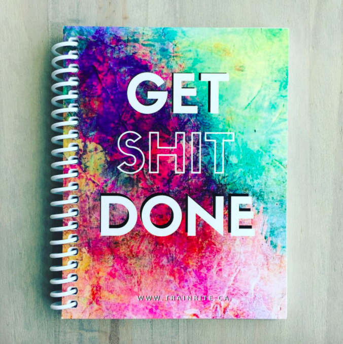 A spiral-bound notebook with the words Get Shit Done on the cover