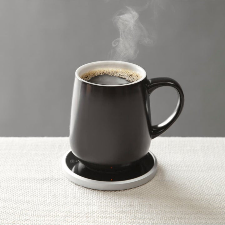 The matte black coffee cup with a black circle coaster under it, keeping the coffee inside warm and with steam coming out of it