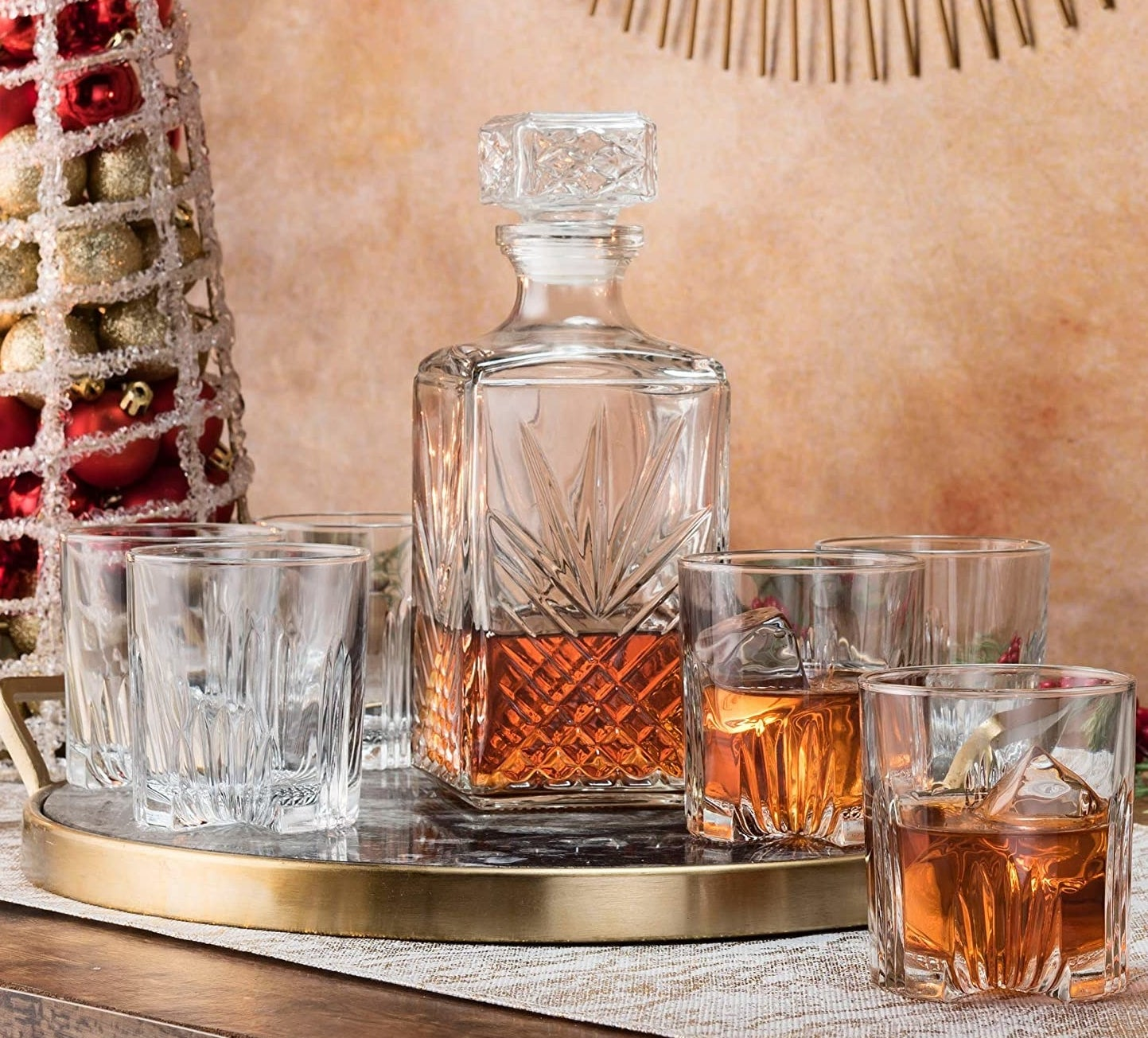 Six glasses beside a whisky decanter on a metallic tray