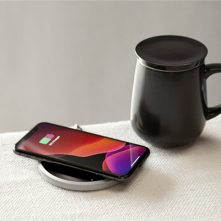 The coffee cup now next to the coaster with a phone on it, showing how it charges it