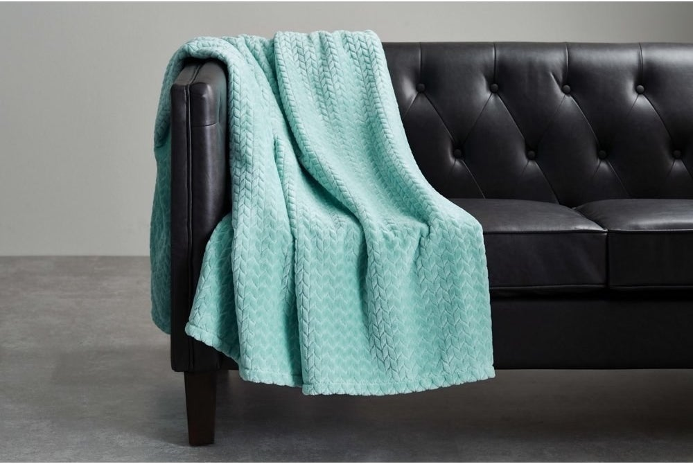 a turquoise throw blanket on a black couch
