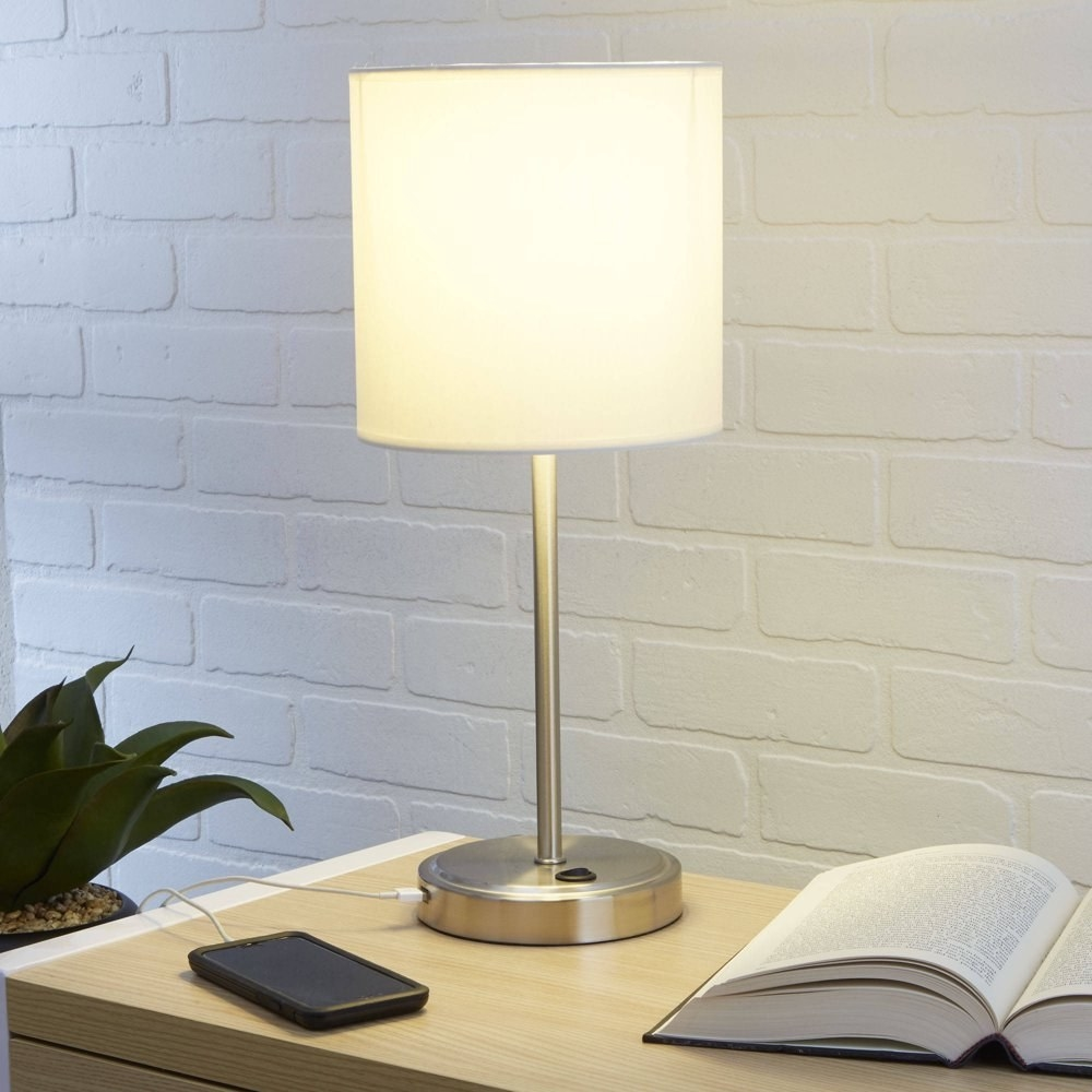 a lamp with a white shade and a silver base charging a phone next to an open book