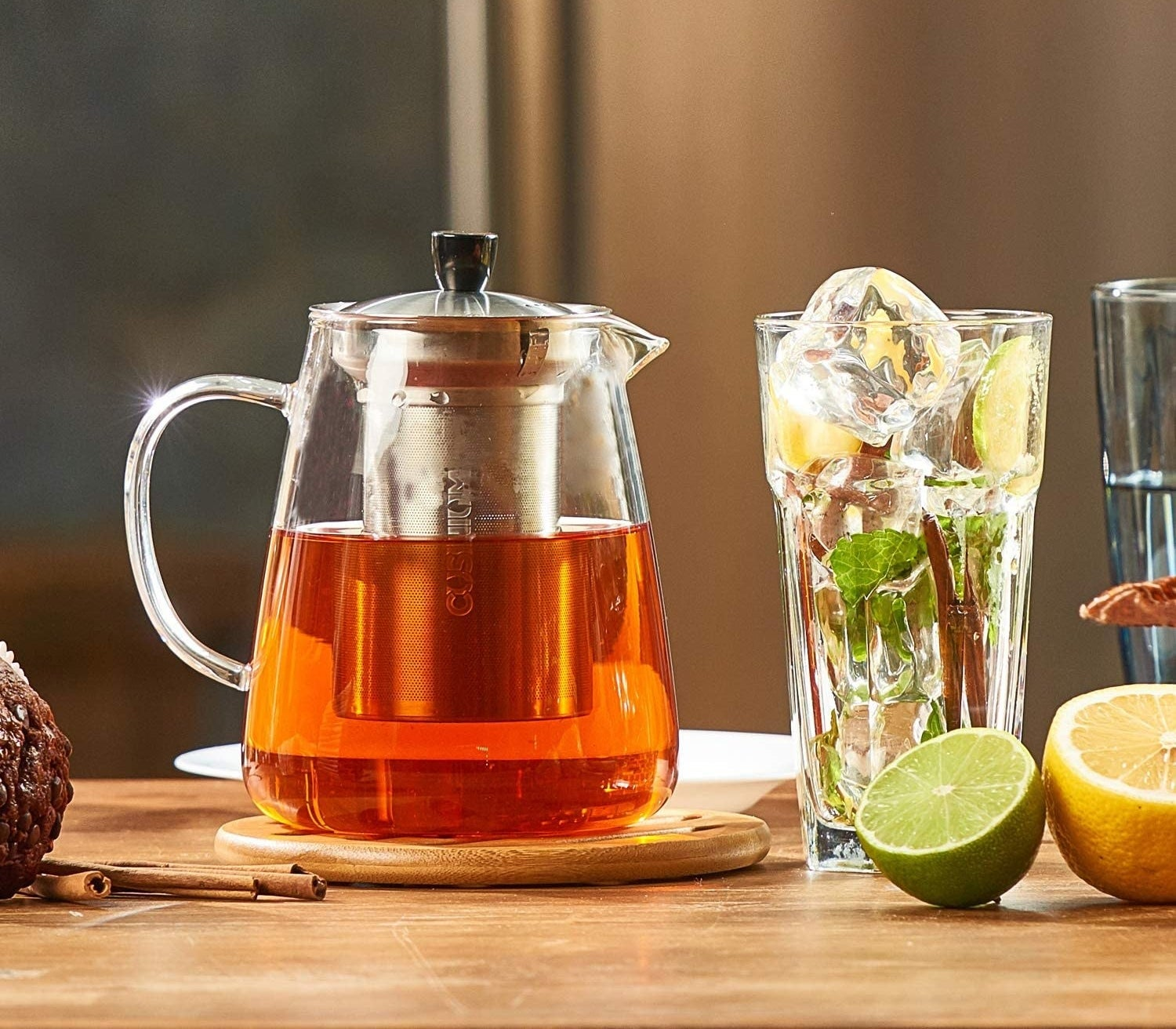 A glass teapot full of tea next to a glass of ice