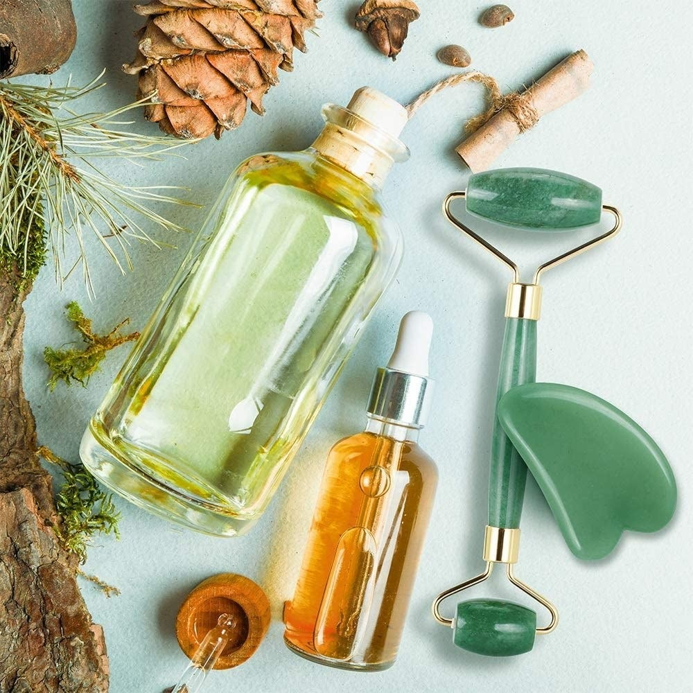 Two bottles of oil beside the double-sided jade facial roller and a jade gua sha tool