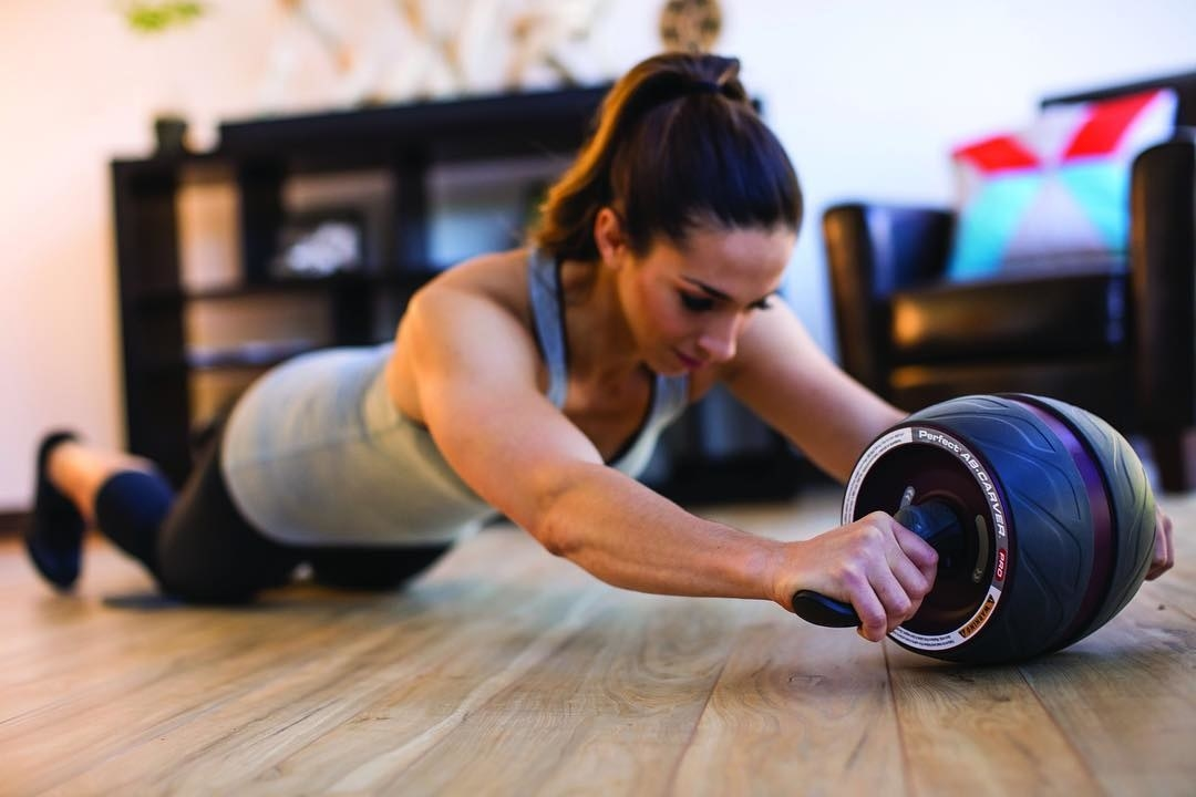 A person using the ab rollers on a floor