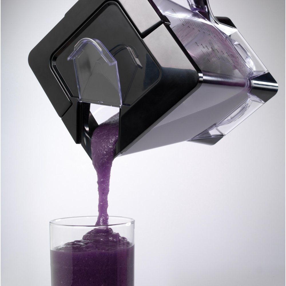 a ninja blender with a balck lid pouring a smoothie into a glass