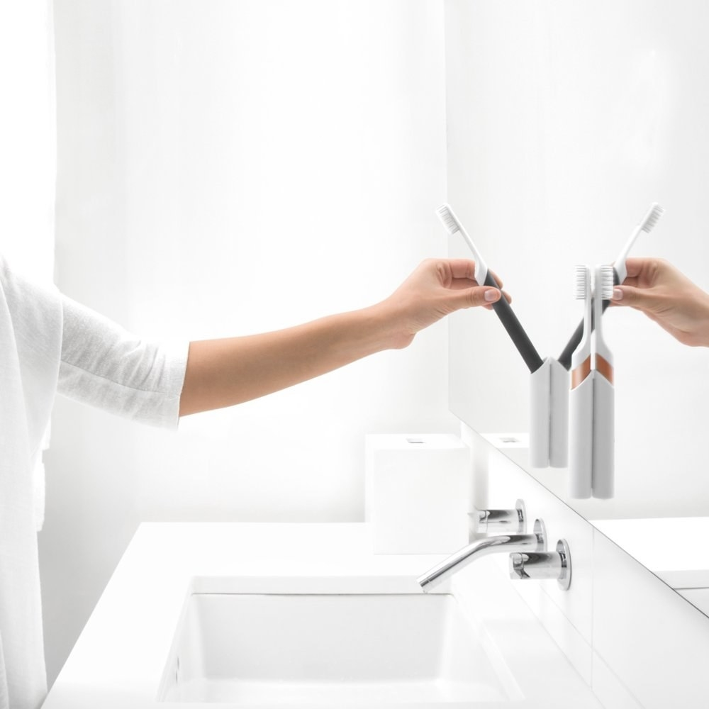 a hand picking up a quip toothbrush from its carrying case that is adhered to the bathroom mirror