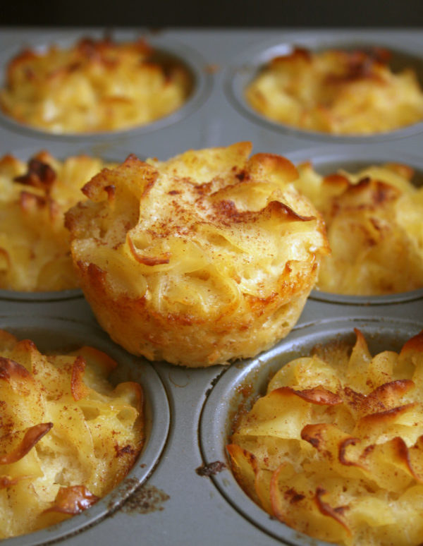 A muffin tin filled with individual noodle kugel muffins.