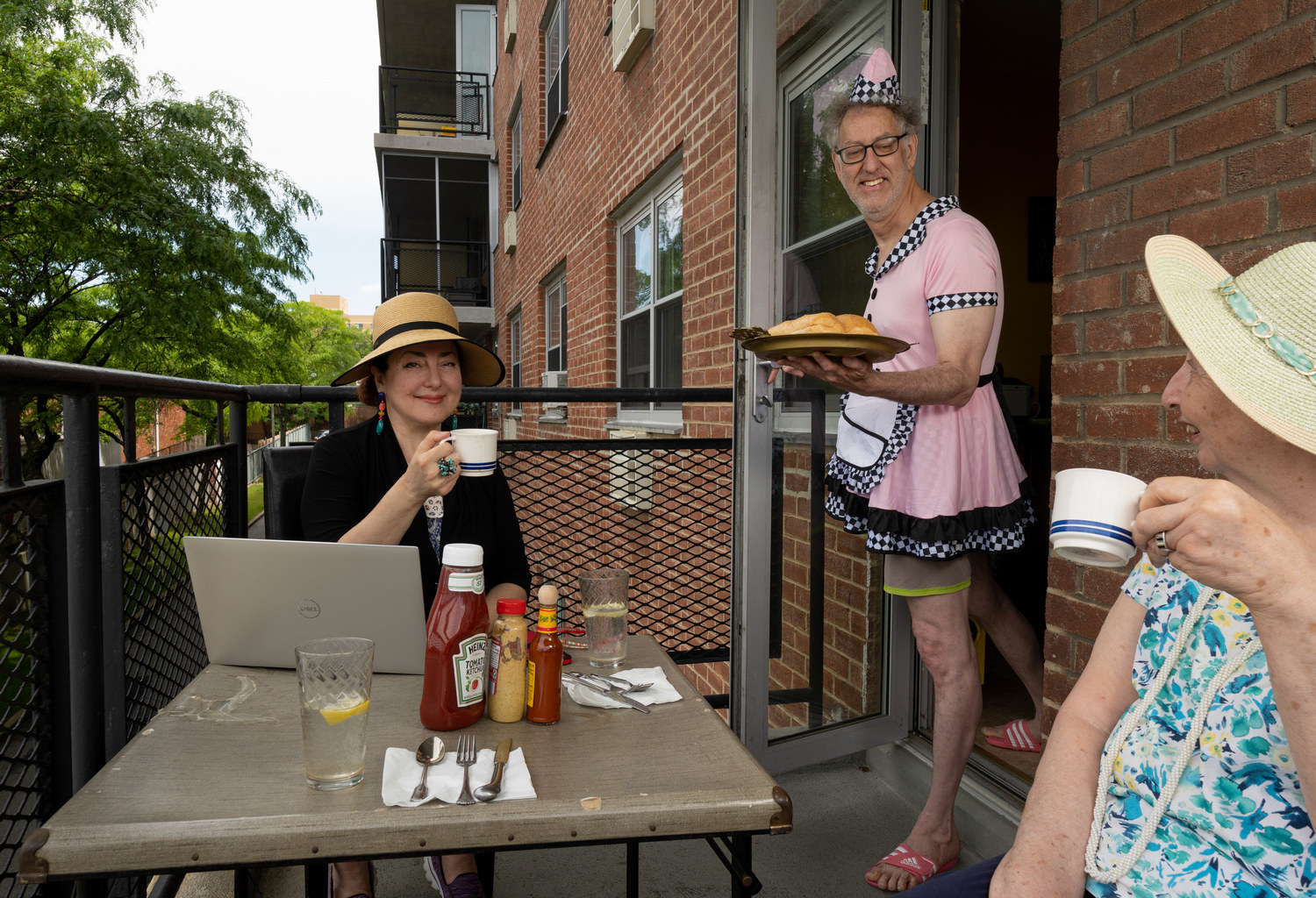 Two women dining on a balcony while a man in a server costume brings them food