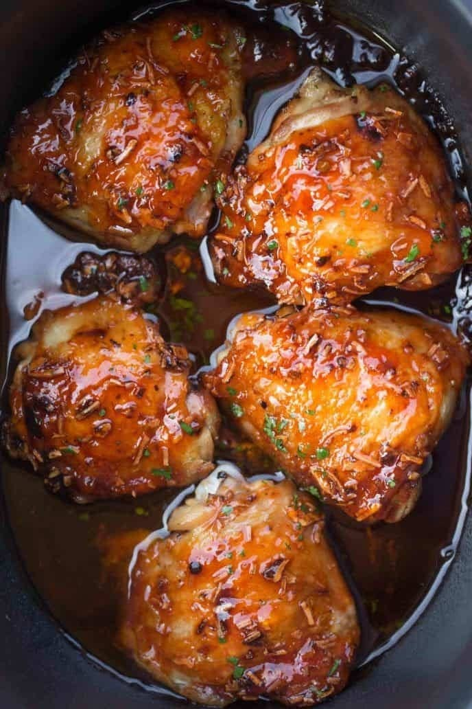 Apricot glazed chicken thighs in a slow cooker.