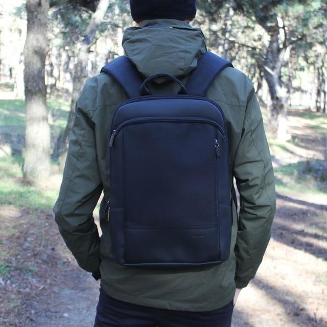 Reviewer wearing the slim black backpack on their back