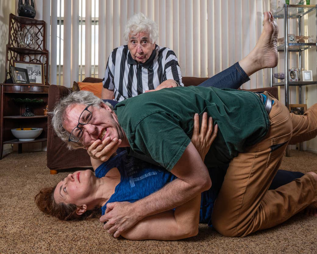 A man and a woman fighting on the floor while a woman in a referee costume looks on