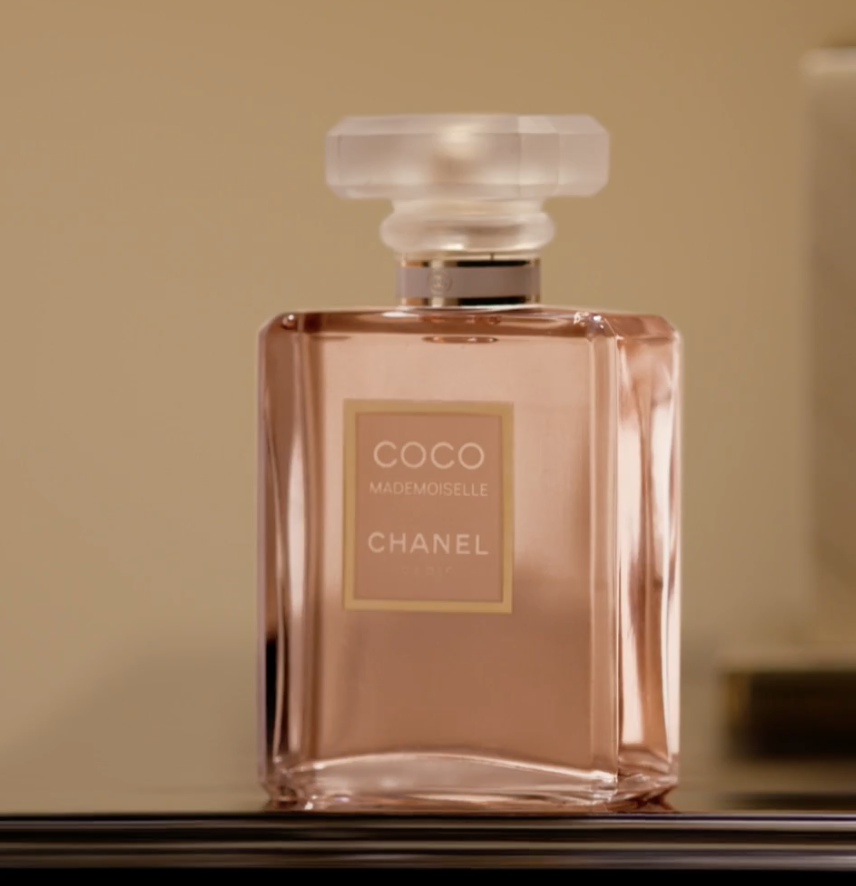 The clear rectangle bottle with light pink perfum inside and a white cap on top with the logo in pink on the front