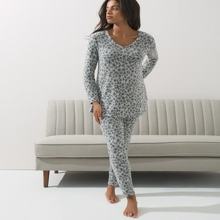 Model wearing the scoop neck long-sleeved pajama top and matching pants in grey with dark grey animal print
