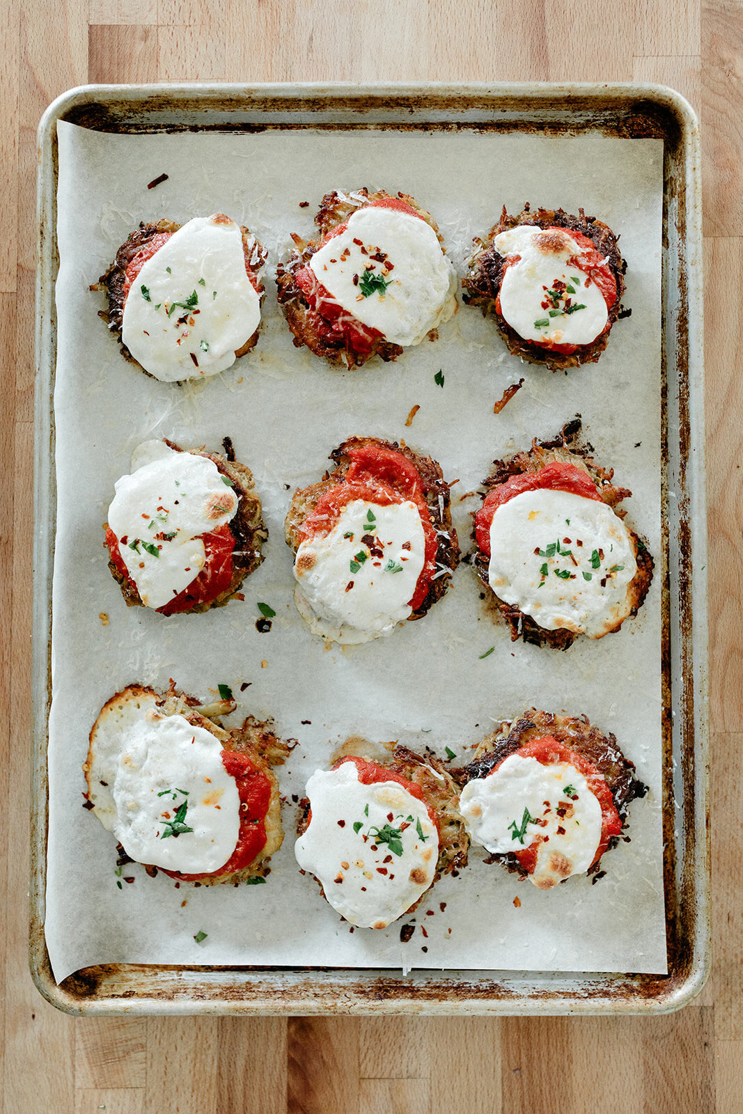 A baking sheet lined with latkes topped with tomato sauce and mozzarella cheese.