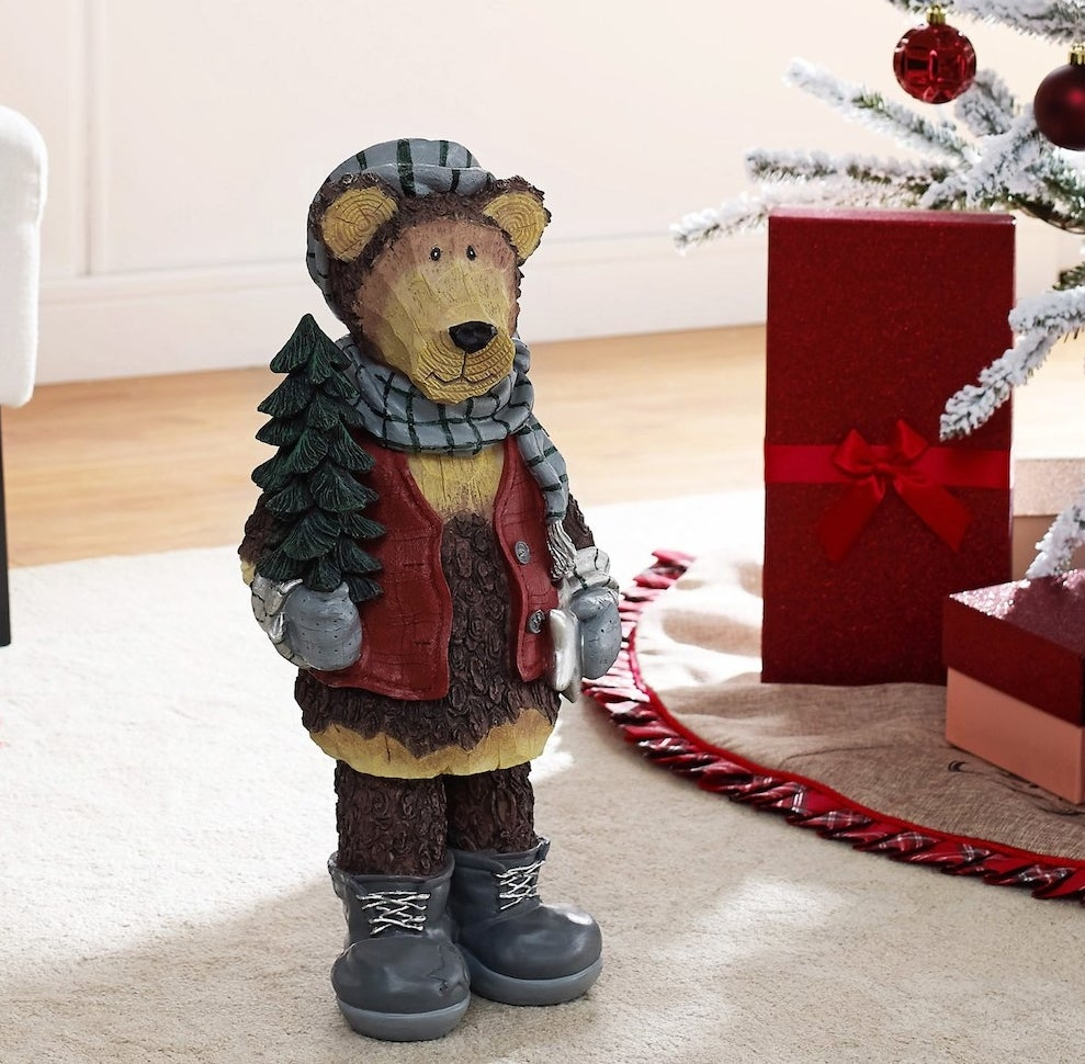 The bear figurine positioned next to a Christmas tree