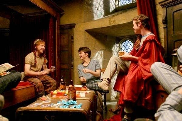 Ron, Harry, and other Gryffindor boys in their dormitory laughing together