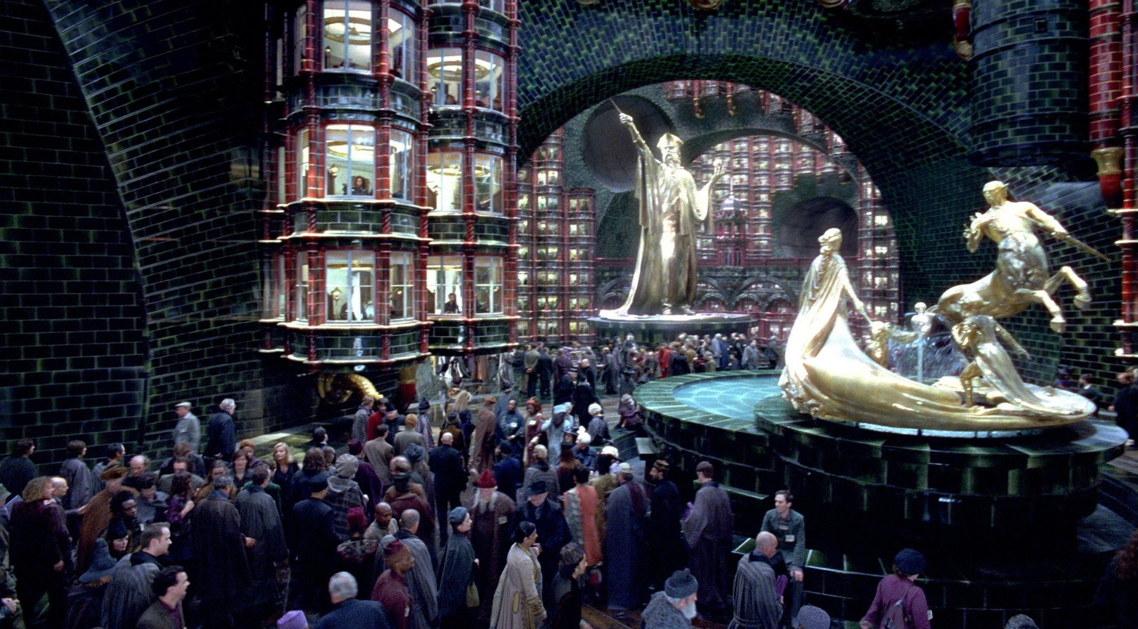 The ministry of magic main entrance with giant gold statues and bustling with workers