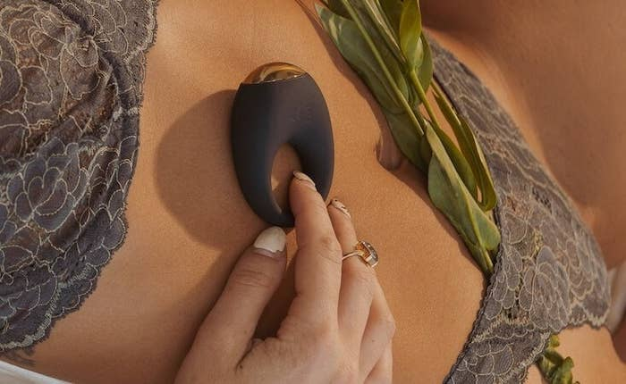 Hand holds black Halo by Bellesa cock ring against model's chest
