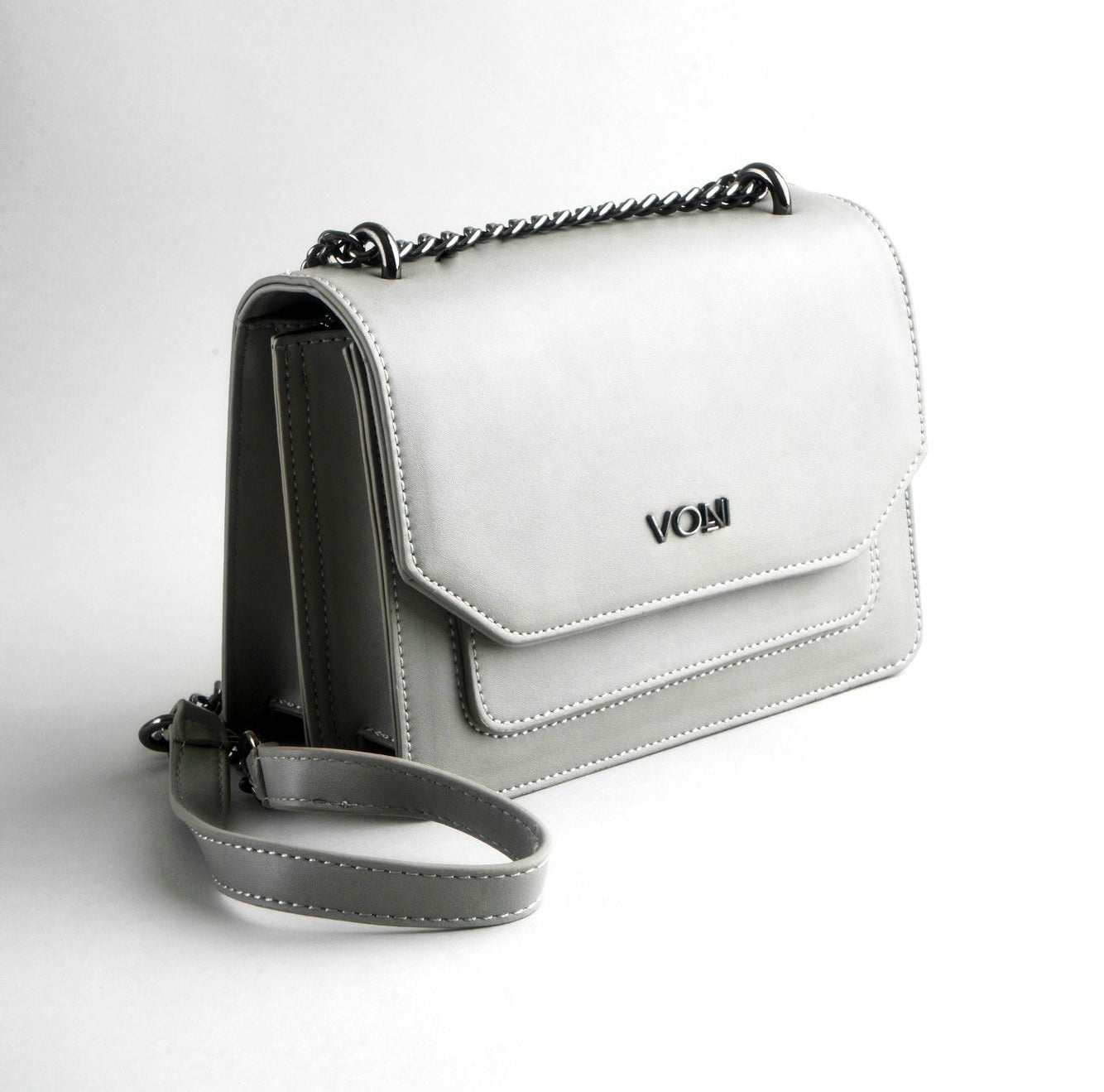 The rectangle-shaped handbag with a silver metal chain strap with a soft part in the center and a front flap, two inner compartments, and front-slip pocket in grey