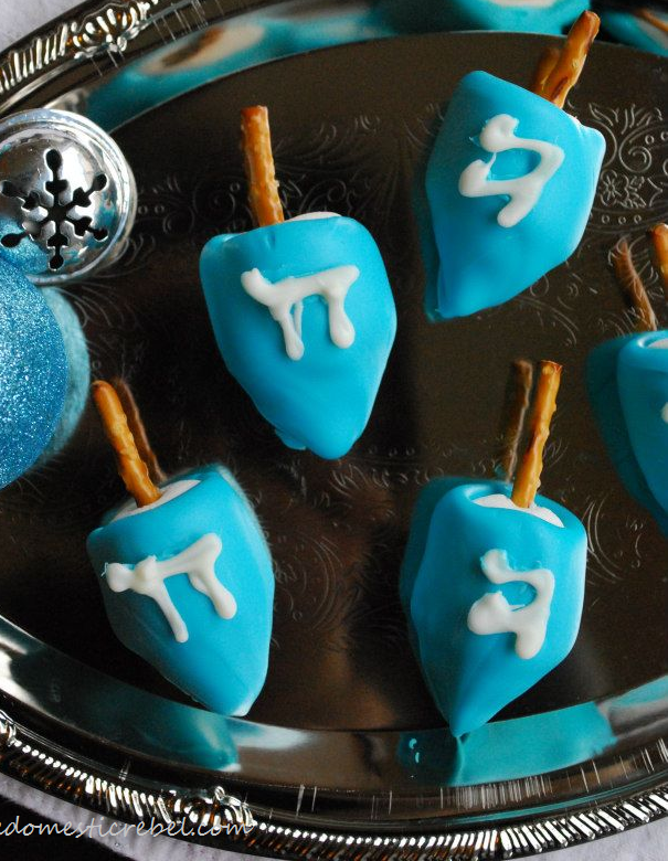 Several chocolate covered marshmallow dreidels with pretzels.